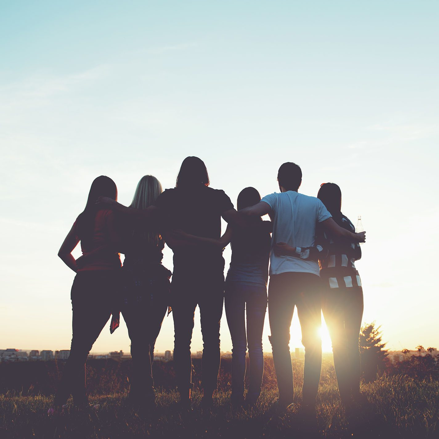 Group of people hugging outdoors; sunset